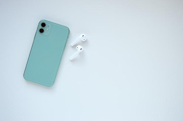 白のワイヤレスヘッドホンを備えたモダンなミントカラーのスマートフォン。フラットレイ