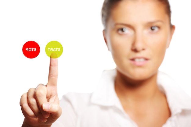 Современная фотография молодой деловой женщины, касающейся кнопки пуска на экране
