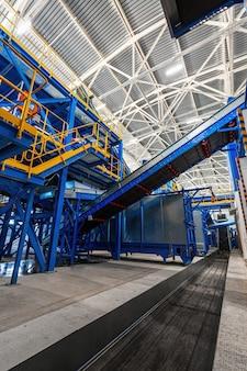Современный завод по сортировке и переработке бытовых отходов и мусора. большой производственный комплекс конвейеров, бункеров.