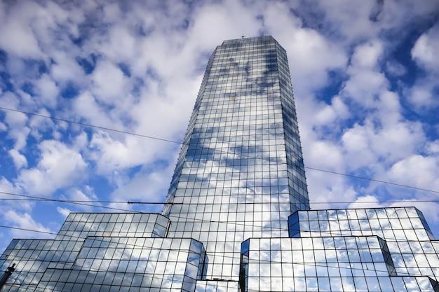 白い雲のワルシャワポーランドと青い空を背景にモダンな反射オフィス超高層ビル