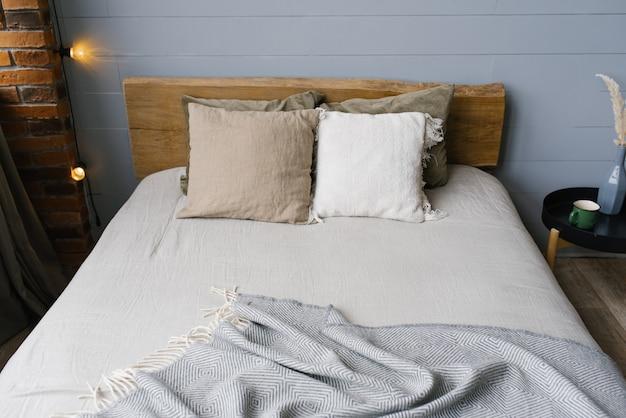 Современная спальня в серых скандинавских тонах с постельным бельем и подушками пастельных тонов. деревянная кровать