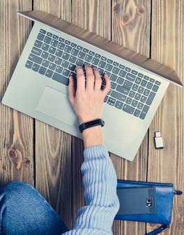Современная молодая девушка сидит на деревянном полу и наслаждается ноутбуком