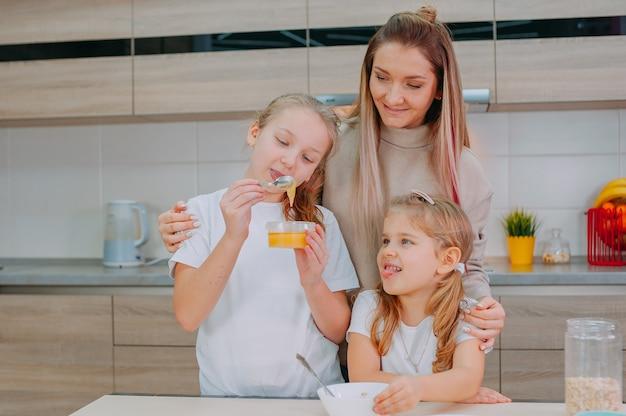 한 엄마와 두 딸이 부엌에서 오트밀에 꿀을 넣습니다.