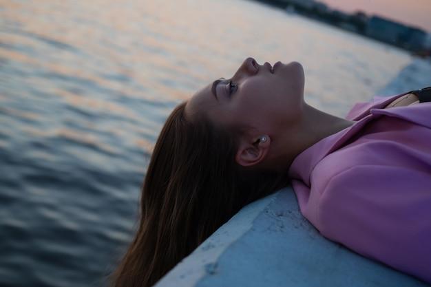 Момент спокойствия в городском пространстве, молодая женщина чувствует расслабление, кладя голову и глядя на небо, лежа на фоне моря.
