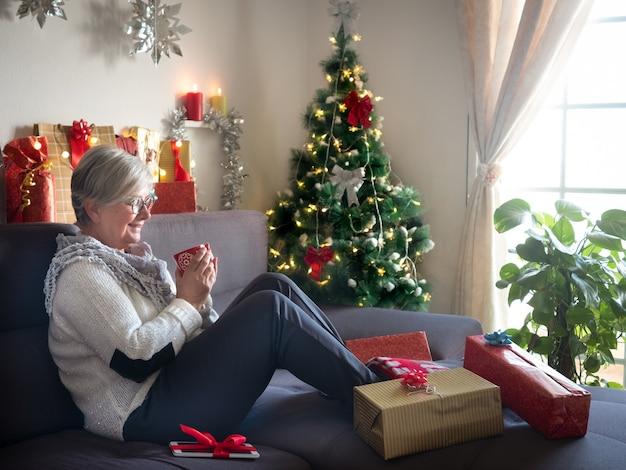 クリスマスプレゼントを用意した後、お茶を飲みながらリラックスしたひととき。背景のクリスマスツリー、キャンドルとライト