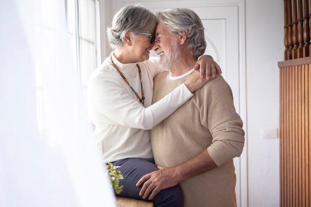 창 앞에서 사랑으로 포옹하는 두 노인의 다정한 순간. 사랑과 행복의 개념