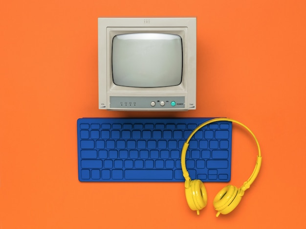 주황색 배경에 파란색 키보드와 노란색 헤드폰이 있는 모니터. 플랫 레이.