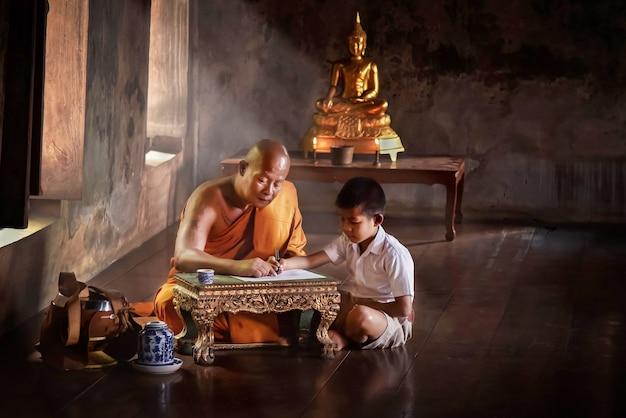 한 승려가 아유타야의 한 사원에서 수요일에 관심이 있는 어린이들에게 종교를 가르치고 있습니다.