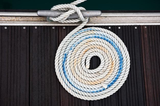나무 부두의 쐐기 주위에 묶인 매듭이있는 계류 로프