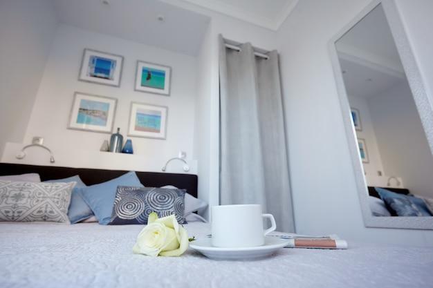 Утренняя газета, чашка чая и белая роза лежат на кровати в ярком