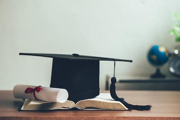 책상 위에 펼쳐진 책에 있는 모타보드와 졸업 두루마리. 교육 학습 개념