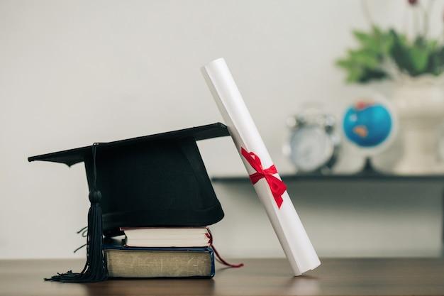 책의 각모판과 책상 위의 졸업 두루마리. 교육 학습 개념