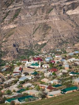 山間の村の中心にあるモスク。ゴールの街並みの風景と田園地帯。ダゲスタン。垂直方向のビュー。