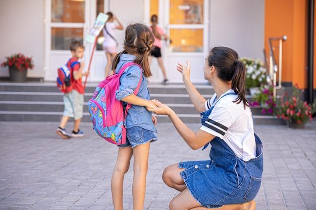 母親が生徒を学校に連れて行き、思いやりのあるお母さんと一緒に幸せな少女が学校に戻ります。