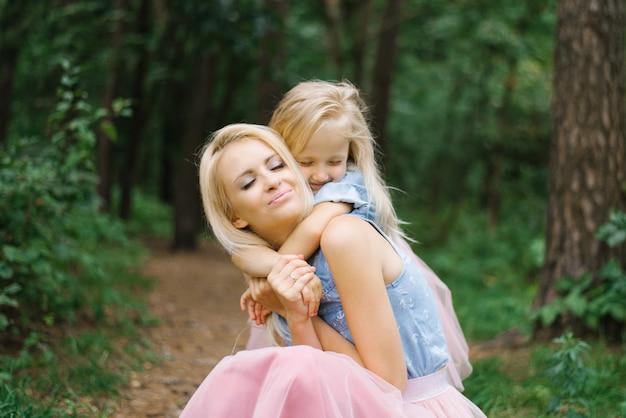 동일한 분홍색 얇은 명주 그물 치마와 블루 데님 셔츠를 입은 어머니와 다섯 살짜리 딸이 공원이나 숲에서 걷고 있습니다. 딸이 어머니를 안아줍니다.