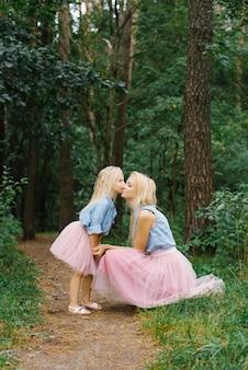 같은 로맨틱 한 옷을 입은 엄마와 다섯 살 딸이 공원이나 숲을 걷고있다.