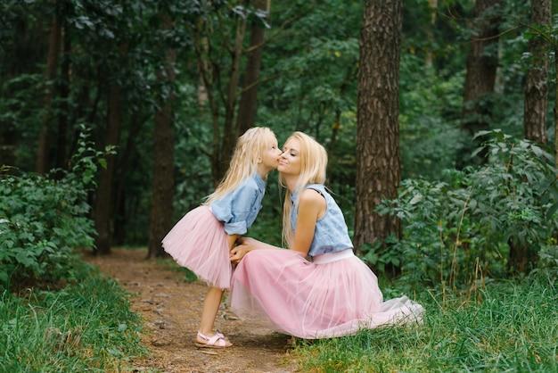 Мать и пятилетняя дочь в одной романтической одежде гуляют по лесу