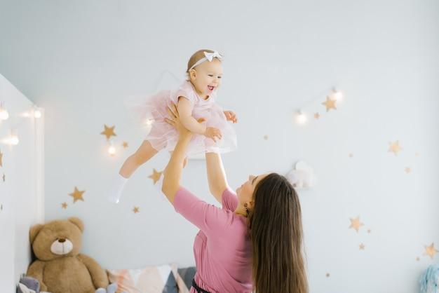 お母さんと小さな子供が子供部屋で遊んでいます。幸せな家族関係。ママは幸せな1歳の娘を投げます。