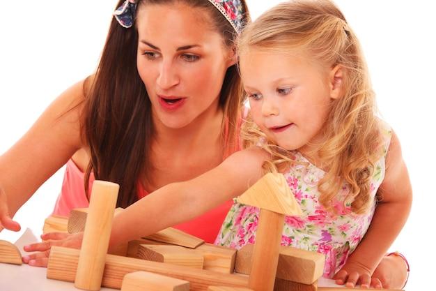 白の上に木製のブロックで建設を構築する母と娘