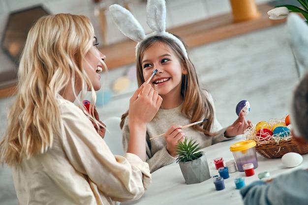 Мать и дочь празднуют пасху, красят яйца кистью. счастливая семья, улыбаясь и смеясь, рисунок на лице. милая маленькая девочка в ушах зайчика готовит праздник.