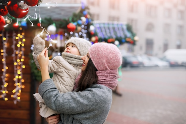 母と娘が街の通りやクリスマスマーケットを歩く