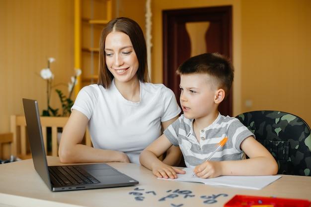 엄마와 아이가 집에서 컴퓨터 앞에서 원격 학습에 참여하고 있습니다. 집에 머물면서 훈련하십시오.