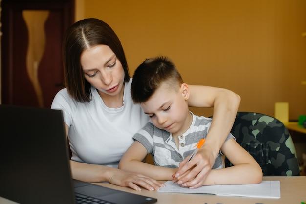 어머니와 그녀의 아이가 집에서 컴퓨터 앞에서 원격 학습에 참여하고 있습니다.