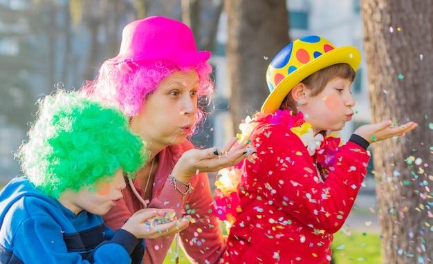 카니발 의상을 입은 어머니와 아이들이 색종이를 가지고 놀고 있습니다.