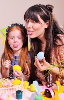 母と娘が卵を描いています。