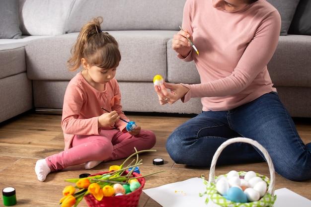 家でイースターエッグを描いている母と娘。