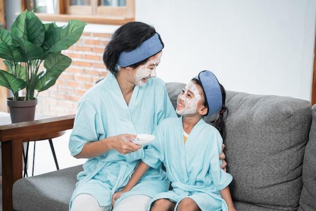 얼굴 마스크를 쓴 어머니와 어린 소녀가 거실 소파에 앉아 서로를 응시합니다.