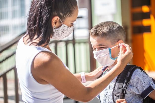 Мать и ее сын надевают защитную маску, возвращаясь в школу во время карантина covid-19.
