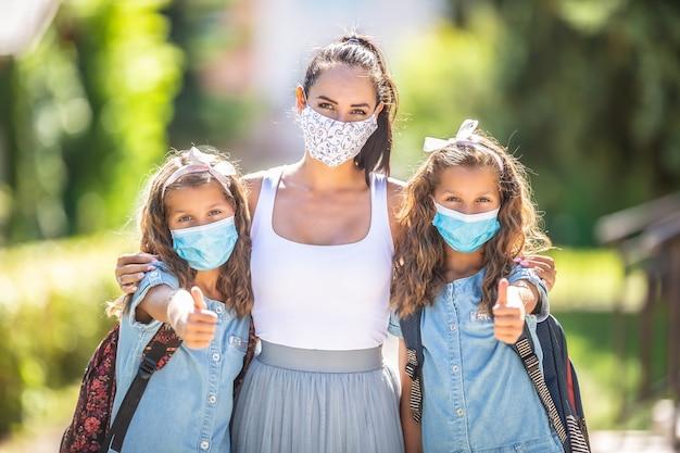 母親と双子の娘は、covid-19検疫中に親指を立てて学校に戻るときに、保護マスクを使用します。