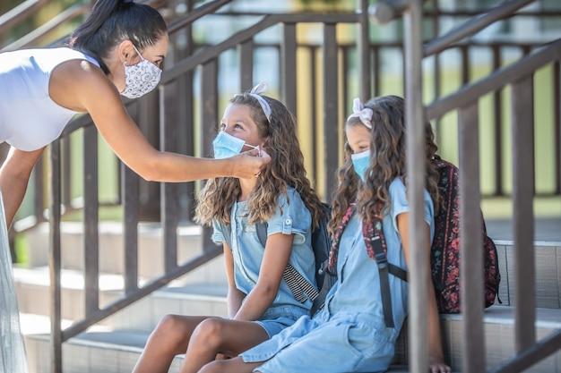 母親と双子の娘は、covid-19検疫中に学校に戻るときに保護マスクを使用します。