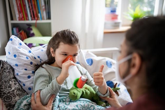 Мать и больная маленькая дочь используют ингалятор в постели у себя дома, концепция коронавируса.