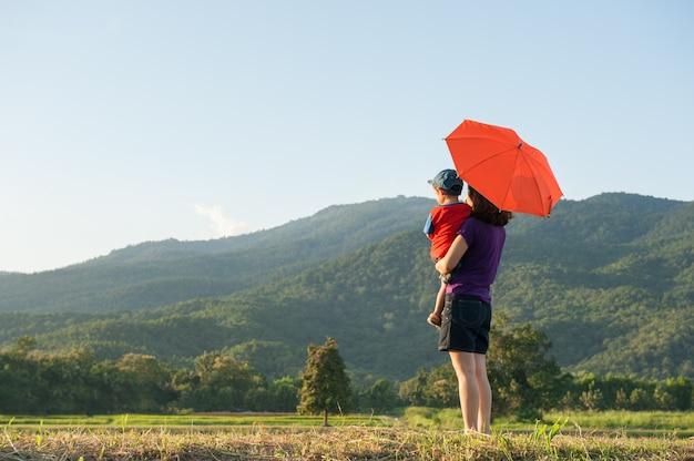 Мать и сын держит зонтик и играют на открытом воздухе