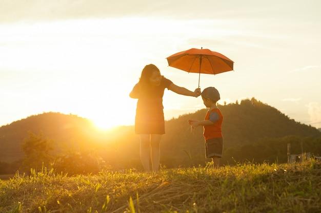 Мать и сын держит зонтик на открытом воздухе на закате Premium Фотографии