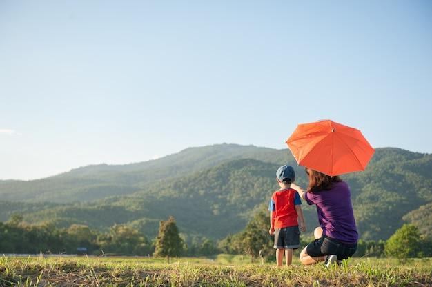 Мать и сын держит зонтик на открытом воздухе на закате