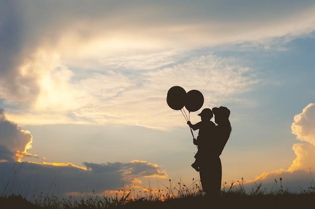 サンセットのシルエットで屋外で遊ぶ母親と息子
