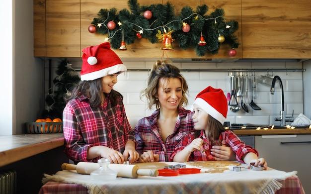 赤い格子縞のシャツと赤い帽子をかぶった母親と2人の若い娘が、クリスマスに飾られたキッチンでクッキーを作る方法を学びます