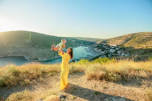 長い黄色のドレスを着た母親が山の頂上に赤ちゃんを抱いて立っている