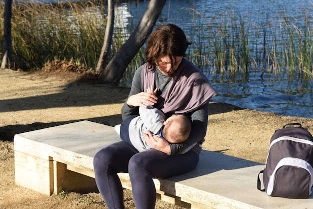 Мать, одетая в спортивную одежду, кормит ребенка грудью