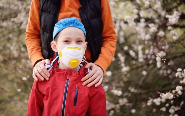Мать обнимает маленького ребенка сына в респираторе на фоне весеннего цветения деревьев во время пандемии коронавируса covid-19.