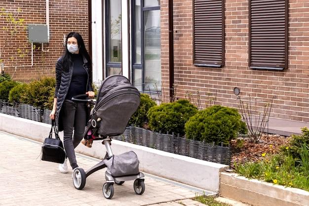 보호 마스크를 쓴 어머니가 유모차를 타고 아기와 함께 거리를 걷는다.