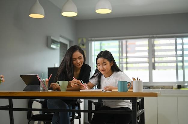 母親が娘と一緒に座って、木製のワーキングデスクで宿題を教えています。