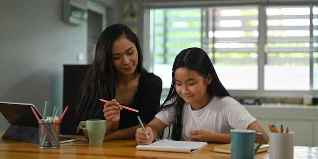 어머니는 딸과 함께 앉아 나무 책상에서 숙제를 가르치고 있습니다.