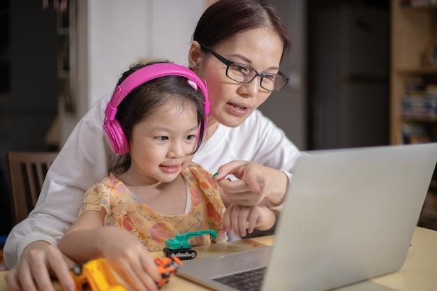 온라인 학습을 돕기 위해 딸을 위해 헤드폰을 착용하고있는 어머니