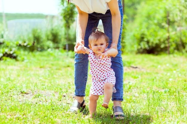 母親が娘の手を庭の芝生に導きます。最初のステップ Premium写真
