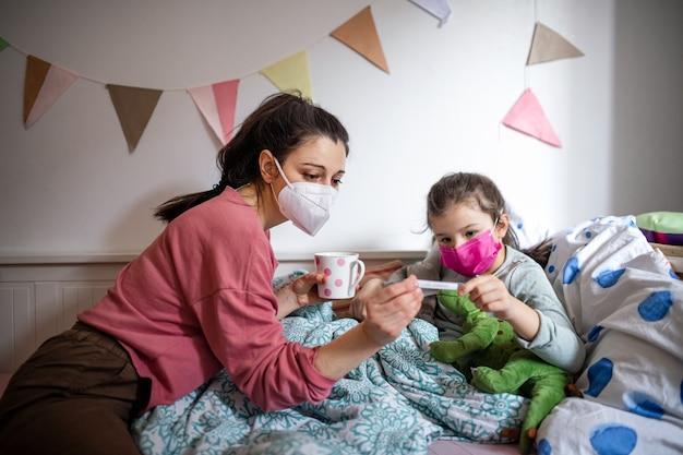 自宅のベッドで病気の小さな娘の世話をしている母親、コロナウイルスの概念。