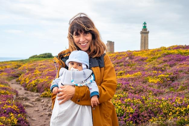 Мать рядом с цветами летом в phare du cap frehel, это морской маяк в кот-д'армор (франция). на вершине мыса фрехеля